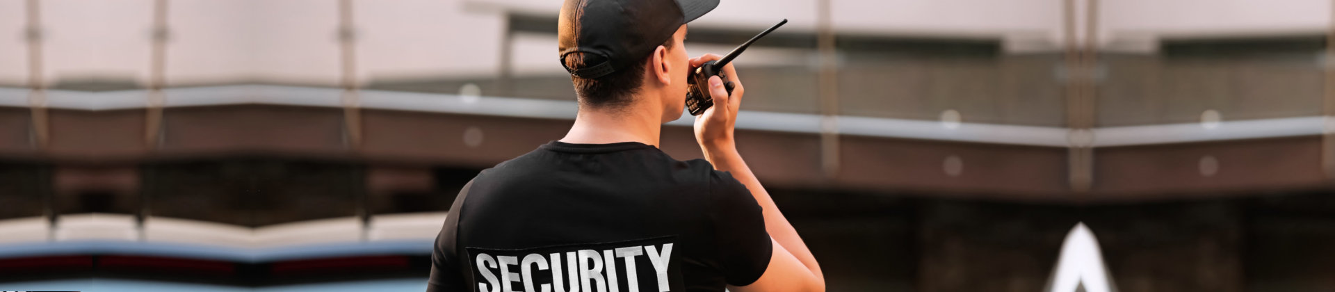 security guard at rear view wearing black cap, t-shirt and holding walkie-talkie