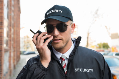 male security guard talking on walkie-talkie