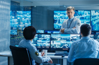 in the security control room chief surveillance officer holds a briefing for two of his subordinates